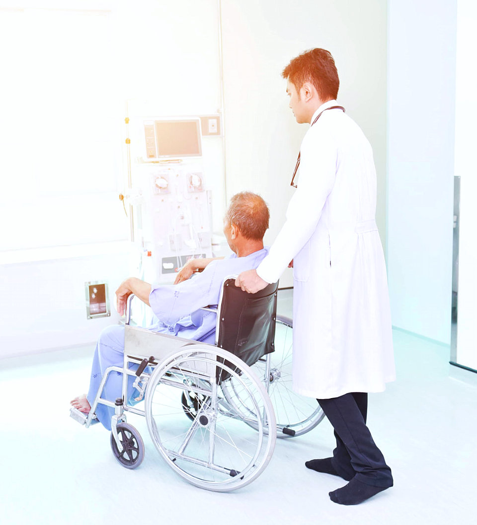 medical personnel pushing an elderly man in a wheelchair